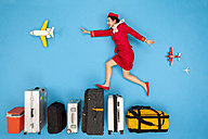 Flight attendant jumping over row of luggage - BAEF01381