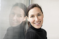 Reflection and portrait of smiling businesswoman wearing black turtleneck pullover - DMOF00027