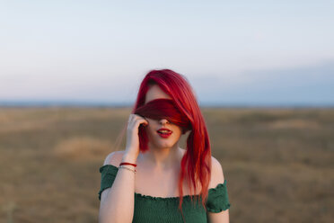 Redheaded woman covering eyes with her hair - JPF00235