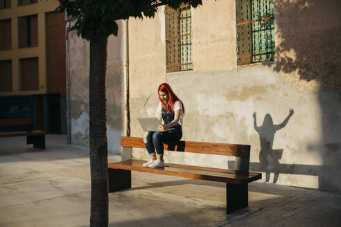 Redheaded woman sitting on bench using laptop - JPF00238