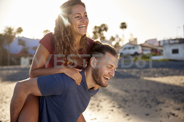 Young man giving his girlfriend a piggyback ride on the beach - PACF00015