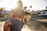 Young man giving his girlfriend a piggyback ride on the beach - PACF00018