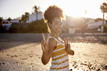 Portrait of woman showing victory sign on the beach - PACF00024