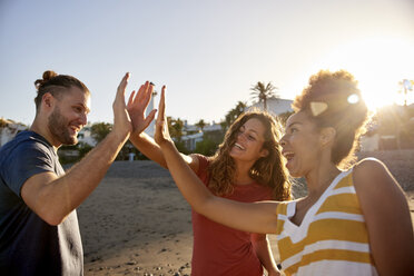 Three friends High Fiving on the beach - PACF00027