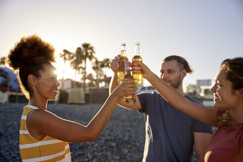 Three friends toasting with beer bottles on the beach - PACF00030