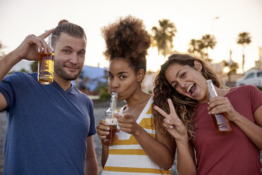 Portrait of three friends with beer bottles having fun on the beach - PACF00039
