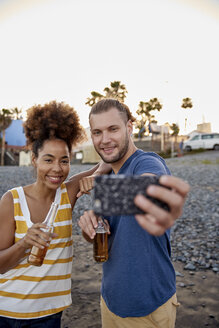 Two friends with beer bottles taking selfie on the beach - PACF00045