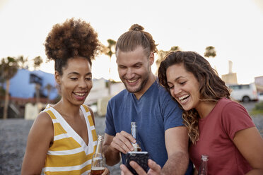 Three laughing friends with beer bottles looking at smartphone on the beach - PACF00048