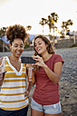 Two laughing friends with beer bottles taking selfie on the beach - PACF00051