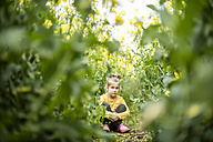 Serious girl sitting in rape field - MOEF00005