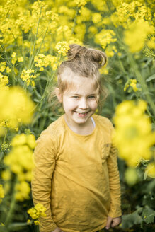 Happy girl standing in rape field - MOEF00008