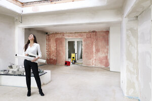 Woman in empty apartment looking around - DMOF00031