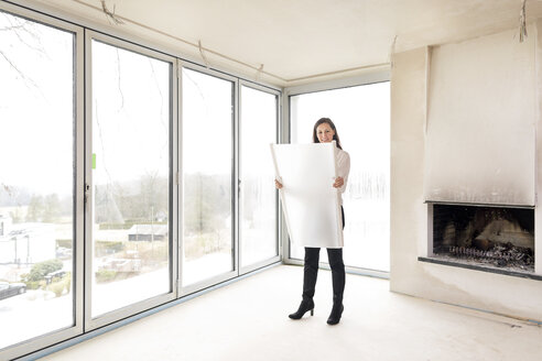 Woman in empty apartment with plan - DMOF00034