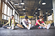 Three young people stretching in gym - HAPF01790