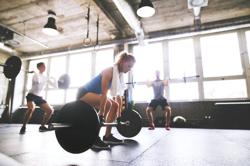 Young woman with training partners preparing to lift barbell in gym - HAPF01814
