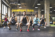 Group of young fit people lifting kettlebells in gym - HAPF01829