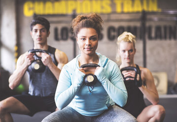 Confident young woman with training partners lifting kettlebell in gym - HAPF01832