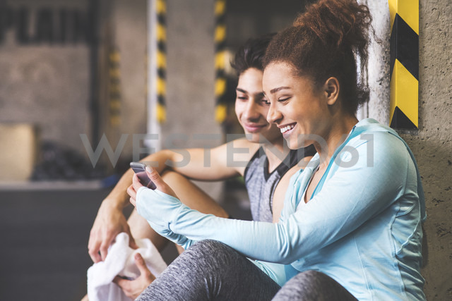 Two smiling athletes sharing cell phone in gym - HAPF01835