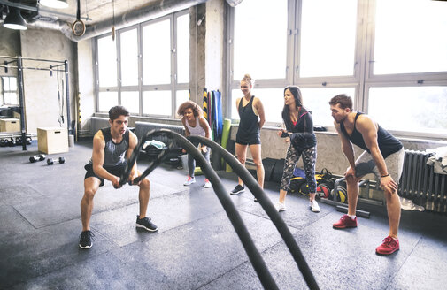 Group of young fit people cheering at man exercising with ropes in gym - HAPF01856