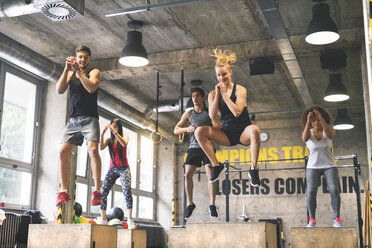 Group of young fit people doing box jumps in gym - HAPF01859