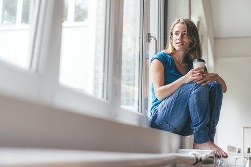 Smiling young woman holding takeaway coffee sitting at the window - KNSF01641
