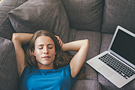 Young woman with laptop lying on couch at home - KNSF01644