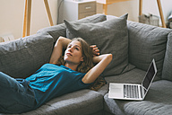 Young woman with laptop lying on couch at home - KNSF01650
