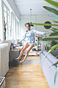 Excited young woman jumping at home - KNSF01656