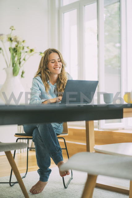 Smiling young woman using laptop at home - KNSF01659