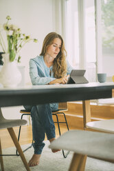 Young woman using tablet at home - KNSF01662