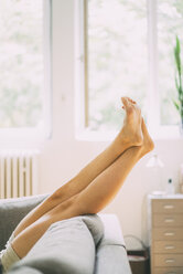 Legs of woman lying on couch at home - KNSF01683