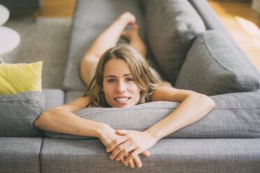 Portrait of young woman relaxing on couch at home - KNSF01686