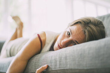 Portrait of young woman relaxing on couch at home - KNSF01689
