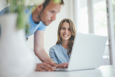 Smiling young woman and man using laptop at home - KNSF01695