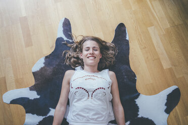 Portrait of smiling young woman lying on fur on the floor - KNSF01704