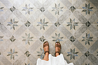 Woman standing on ornate tiled floor - GEMF01699