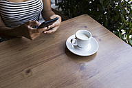 Young woman sitting in a coffee shop using cell phone, partial view - ABZF02146