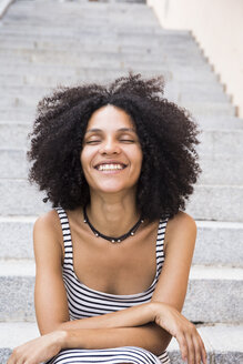 Portrait of laughing woman with eyes closed sitting on stairs - ABZF02152