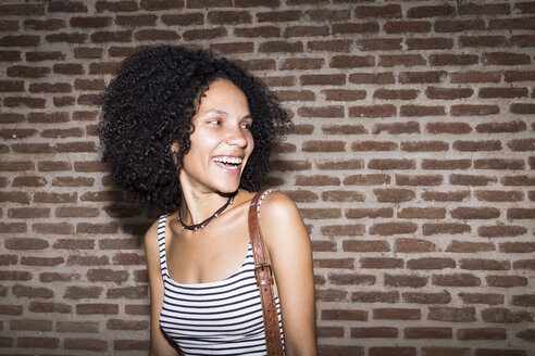 Portrait of laughing woman in front of brick wall at night - ABZF02158