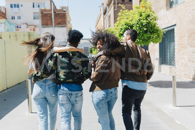 Rear view of stylish friends walking on urban street - GIOF02817