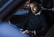 Businessman using laptop in car at night - UUF10877