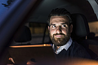 Portrait of confident businessman in car at night - UUF10880