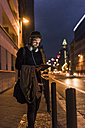 Stylish young man with tablet on urban street at night - UUF10883