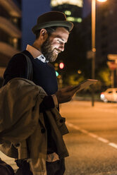 Stylish young man with tablet on urban street at night - UUF10886