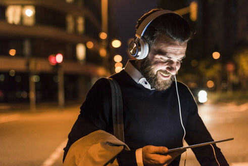 Smiling young man with tablet and headphones on urban street at night - UUF10889