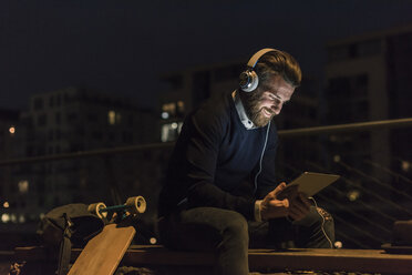 Smiling young man with tablet and headphones in the city at night - UUF10892