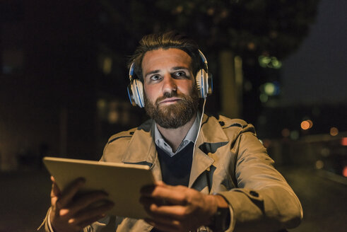Young man with tablet and headphones in the city at night - UUF10895