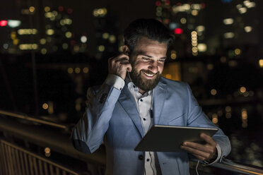 Smiling young man with tablet and earphone on urban bridge at night - UUF10904