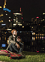 Smiling young man with guitar and cell phone sitting at urban riverside at night - UUF10910