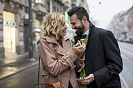 Happy business couple with cell phones in the city - MAUF01103
